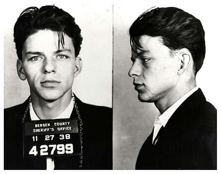 "Pop singer Frank Sinatra poses for a mug shot after being arrested and charged with ""carrying on with a married woman"" in 1938 in Bergen County, New Jersey. Photo: Michael Ochs Archives / Michael Ochs Archives"