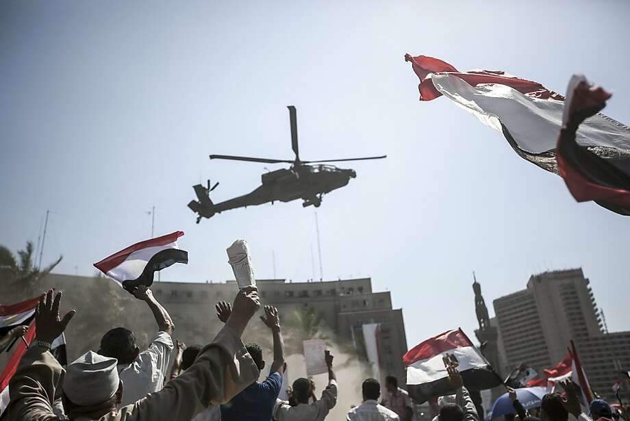 Opponents of ousted Egyptian President Mohammed Morsi watch a military helicopter fly over their demonstration in Cairo's Tahrir Square. Photo: Narciso Contreras, New York Times