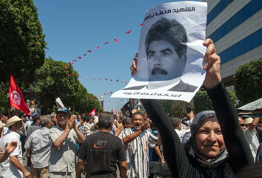 A protester holds a picture of assassinated opposition politician Mohammed Brahmi at a demonstration. Photo: Amine Landoulsi, Associated Press