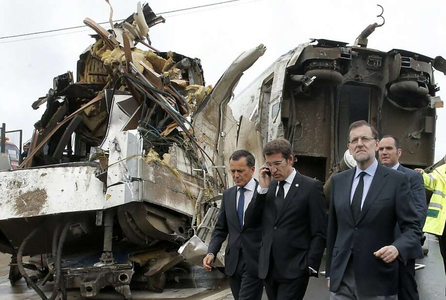 Spain's Prime Minister Mariano Rajoy (R) and Galicia's regional President Alberto Nunez Feijoo (2nd L) visit on July 25, 2013 in Santiago de Compostela, the site where a speeding train derailed on July 24, killing 78 people and leaving 178 injured. Spanish police said on July 26 they have detained the driver of the speeding train that crashed in the nation's deadliest rail disaster in decades, accusing him of criminal recklessness.   AFP PHOTO / POOL / LAVANDEIRA JR.LAVANDEIRA JR./AFP/Getty Images Photo: Lavandeira Jr., AFP/Getty Images