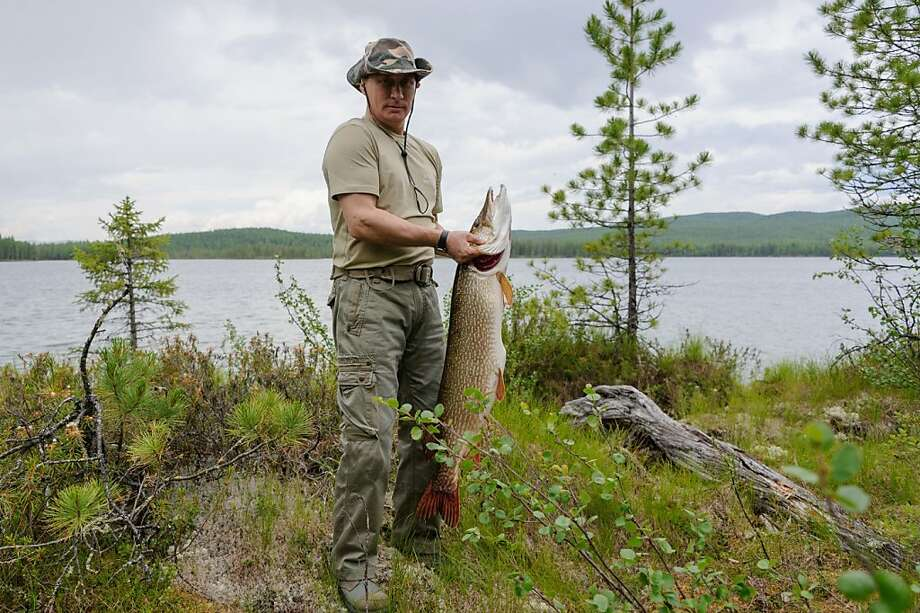 Catch of the day:Russian President Vladimir Putin proudly shows off a huge pike he caught in Russia's Tyva region 