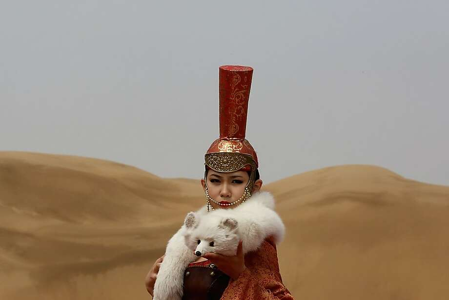 Desert fox: A model performs in a traditional Mongolian costume in the Xiangshawan Desert, also called the Sounding Sand Desert, in Ordos, China's Inner Mongolia Autonomous Region. Xiangshawan is a tourist resort known for its noisy sands, which make the sound of automotive engines as they slide down a 330-foot hill, a natural phenomenon that has yet to be explained. Photo: Feng Li, Getty Images
