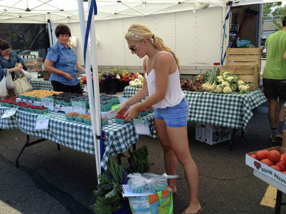 Devan Alusik, one of five shoppers employed by Fresh Nation, selects CT-grown produce from the Riverbank Farms stand at a Fairfield County-area farmers' market. Fresh Nation, founded by Greenwich residents Anthony and Melanie Lee, gathers food from farmers' markets around the county and delivers it, via online orders, to customers. Photo: Contributed Photo