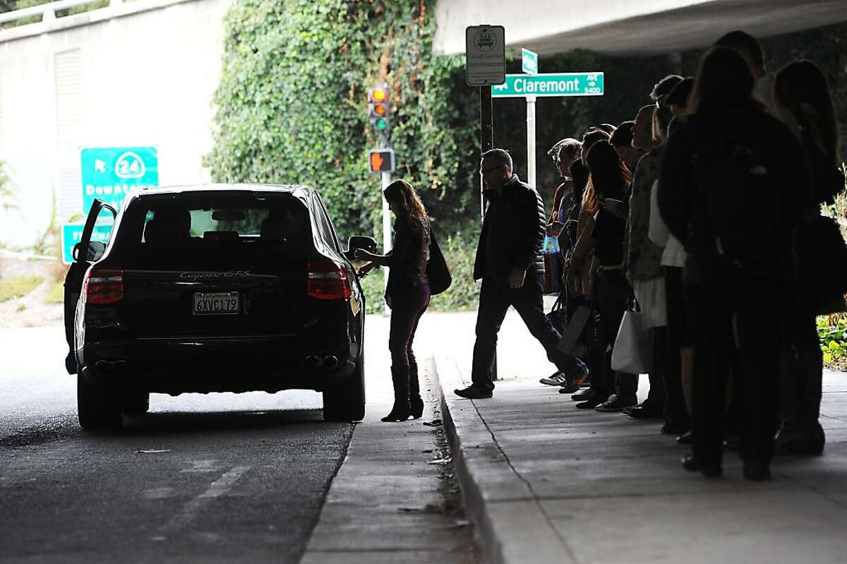 Casual carpoolers wait for rides on Hudson St. near the 24 freeway entrance during the morning commute on Friday, July 26, 2013, in Oakland, California.
