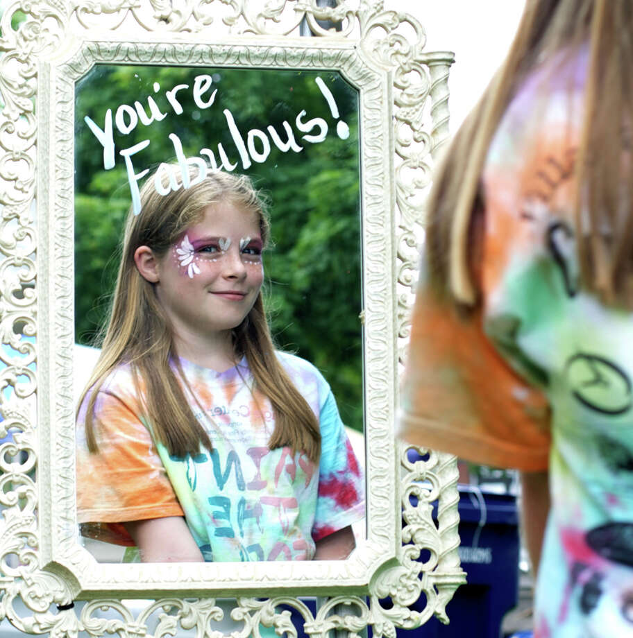 "Kaitlin Dandini, 9, of New Milford is reminded ""you're fabulous!"" as she takes a quick glance at her face painting courtesy of artists at the Village Center for the Arts booth during the Greater New Milford Chamber of Commerce's 46th annual Village Fair Days. July 26, 2013 Photo: Trish Haldin"