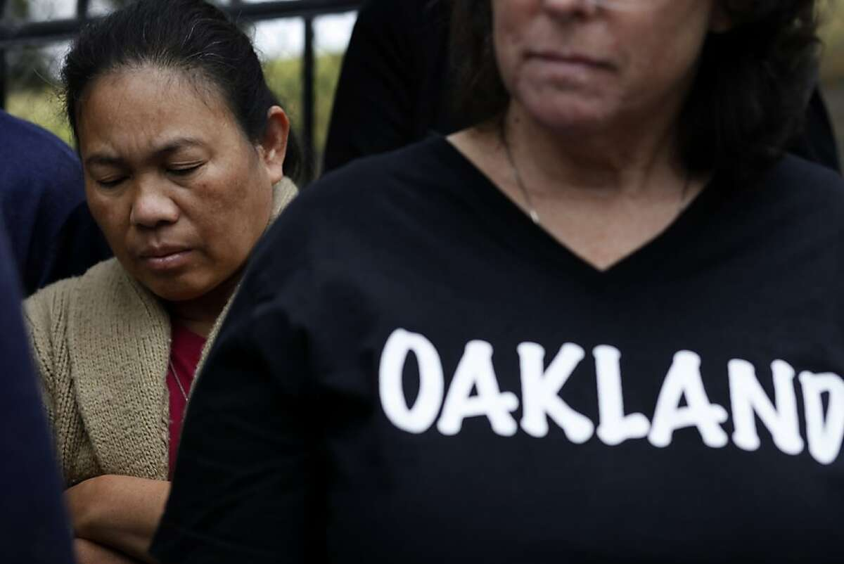 Nora Gonzalez, left, bows her head as she and other neighbors speak out with Oakland's City Council on safety, Friday July 26, 2013, at the memorial for Judy Salamon, who was the city's 56th homicide this year in Oakland, Calif. Nora and her husband Carlos Gonzalez moved to Oakland one year ago and have already been burglarized.