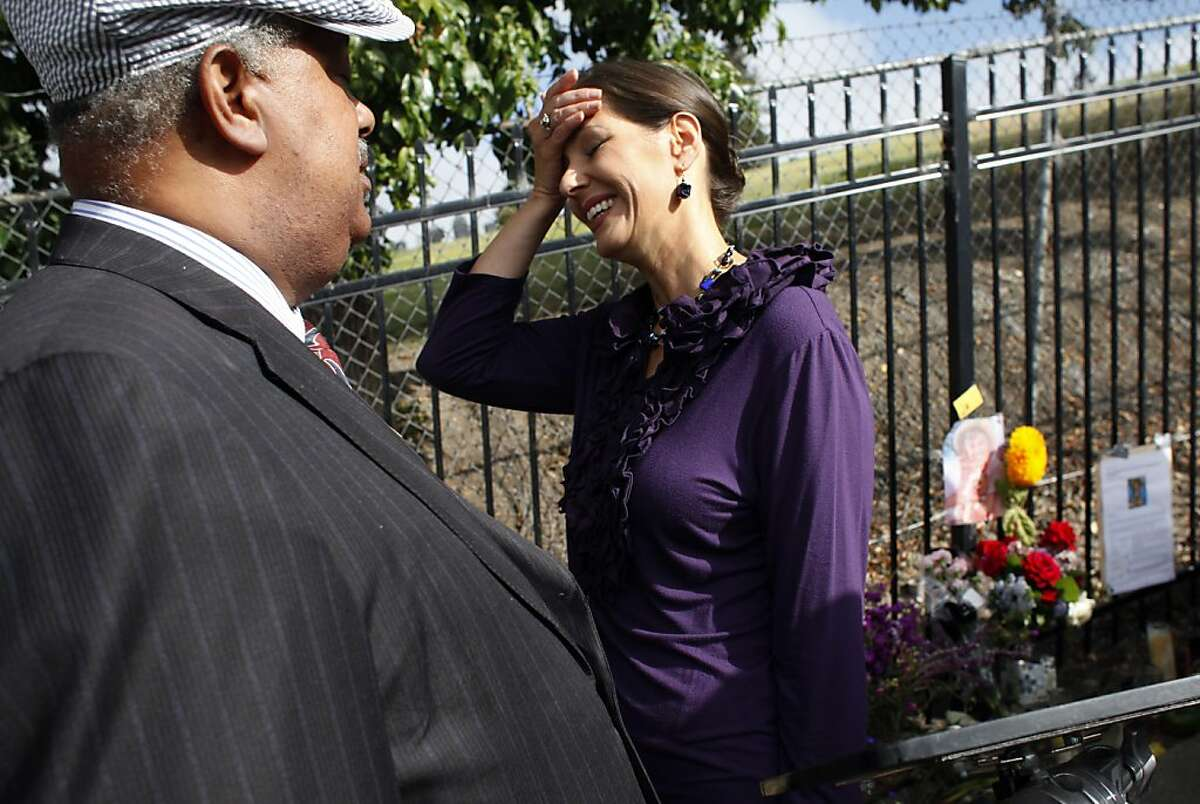 Oakland District 4 Councilmember Libby Schaaf reacts as she talks with Reverend Greggory Brown, as the groop gathers to speak out on the violence, Friday July 26, 2013, at the memorial for Judy Salamon in Oakland, Calif.