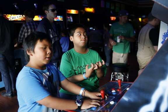 Andrew Saephan, right, reacts to losing Mortal Kombat II while Joshua Saephan, left, continues to play at the High Score arcade in Alameda, California on July 12, 2013.