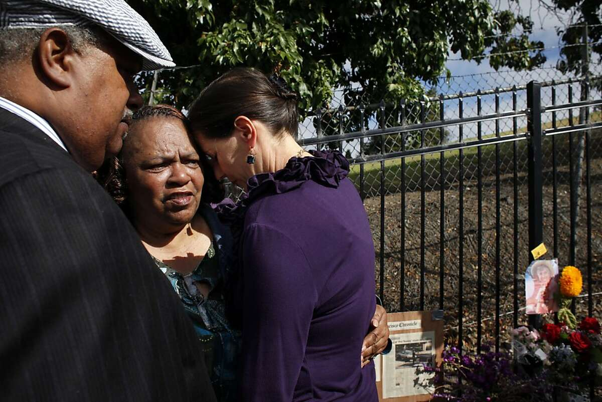 Reverend Greggory Brown, Barbara Taylor and Oakland District 4 Councilmember Libby Schaaf comfort each other as the gathers to speak out on the violence, Friday July 26, 2013, at the memorial for Judy Salamon, who was the city's 56th homicide this year in Oakland, Calif.
