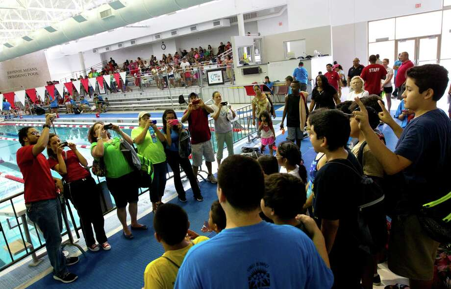 Friends and family take photos of competitors after Splashdown at the Harris County Aquatics Center, Friday, July 26, 2013, in Houston. Splashdown is a showcase event for the free Harris County Street Olympics' summer program offered to boys and girls who learned to swim over the summer. Also, those who already have that skill take courses to perfect their swim strokes. Photo: Cody Duty, Houston Chronicle / © 2013 Houston Chronicle