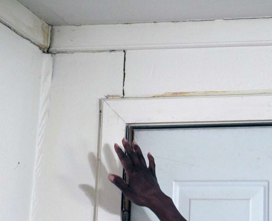 Gloria Lilly points to a crack in a wall of her home in the 3200 block of Exchange street Wednesday, July 24, 2013, in Houston. The city water lines in Lilly's neighborhood have had multiple breaks and service interruptions in addition to flooding under her home from the leaks. Photo: James Nielsen, Houston Chronicle / © 2013  Houston Chronicle