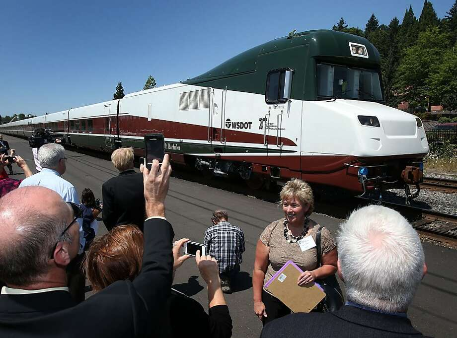 Local dignitaries welcome the arrival of the Mt. Bachelor, a 13-car trainset that is Oregon's first state-owned regular passenger service train, as it pulls into the downtown Amtrak Station in Eugene, Ore. Friday, July 26, 2013.(AP Photo/The Register-Guard, Brian Davies) Photo: Brian Davies, Associated Press
