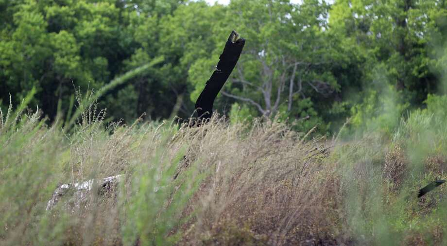 A blade is all that is visible through the weeds and grass at the crash scene. The copter was a total loss. Photo: Karen Warren, Staff / © 2013 Houston Chronicle