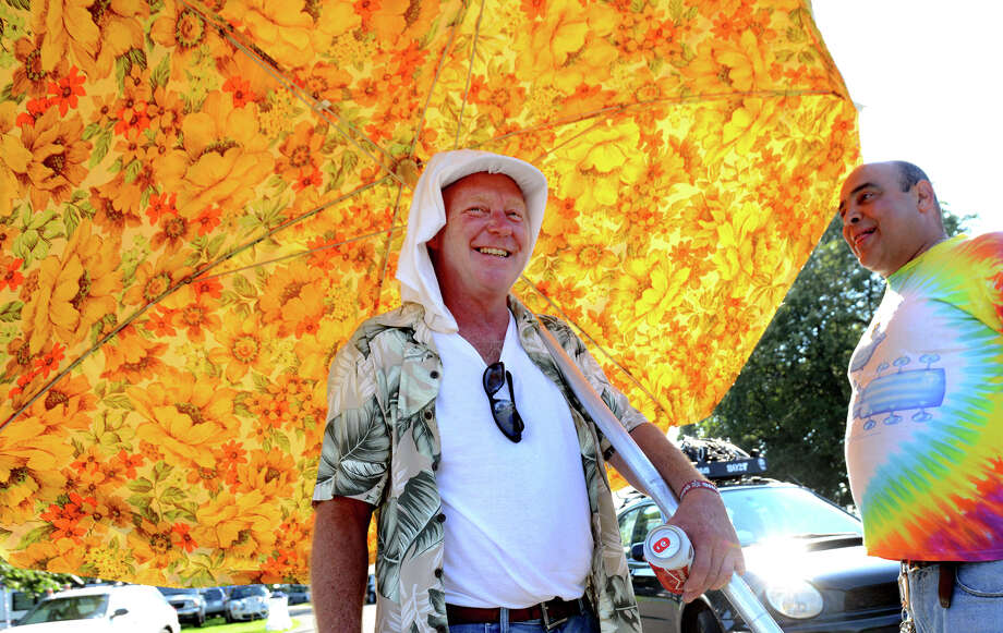 Rob Heltzel, of Bridgeport, walks around with a large deck umbrella for shade while at 18th Annual Gathering of the Vibes music festival at Seaside Park in Bridgeport, Conn. on Friday July 26, 2013. At right is his friend Tommy Carbone. Photo: Christian Abraham / Connecticut Post freelance