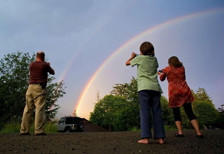 Juneau residents photograph a particularly intense rainbow in Juneau, Alaska, on Tuesday, July 23, 2013. (AP Photo/The Juneau Empire, Michael Penn) Photo: Michael Penn, Associated Press