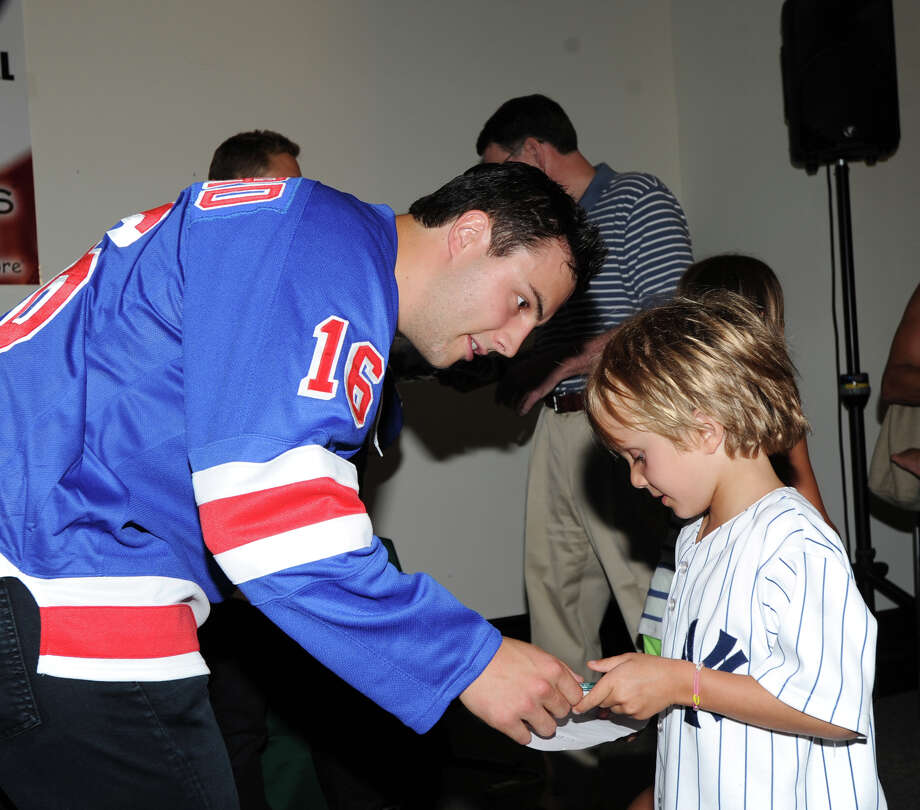 At left, Derick Brassard of the New York Rangers gives an autograph to Mason St. Louis, 5, of Greenwich, during the Cam Atkinson Keep Hope Alive Festival to benefit the Marty Lyons Foundation at Old Town Hall in Stamford, Friday night, July 26, 2013. Mason is the son of Tampa Bay Lightining star, Martin St. Louis. Photo: Bob Luckey / Greenwich Time