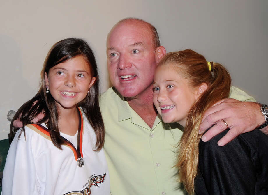 At center, former N.Y. Jet football star Marty Lyons poses with Greenwich sisters, M.K. Braun, 9, at left, and Molly Braun, 10, during the Cam Atkinson, center, of the Columbus Blue Jackets, smiles during the Cam Atkinson Keep Hope Alive Festival to benefit the Marty Lyons Foundation at Old Town Hall in Stamford, Friday night, July 26, 2013. The Marty Lyons FoundationâÄôs mission is granting wishes to children with terminally ill and life threatening illnesses Photo: Bob Luckey / Greenwich Time