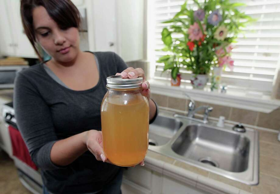 Monika Marine displays a jar of city water that came out of the faucet in her northeast Houston home Wednesday. Photo: James Nielsen, Staff / © 2013  Houston Chronicle