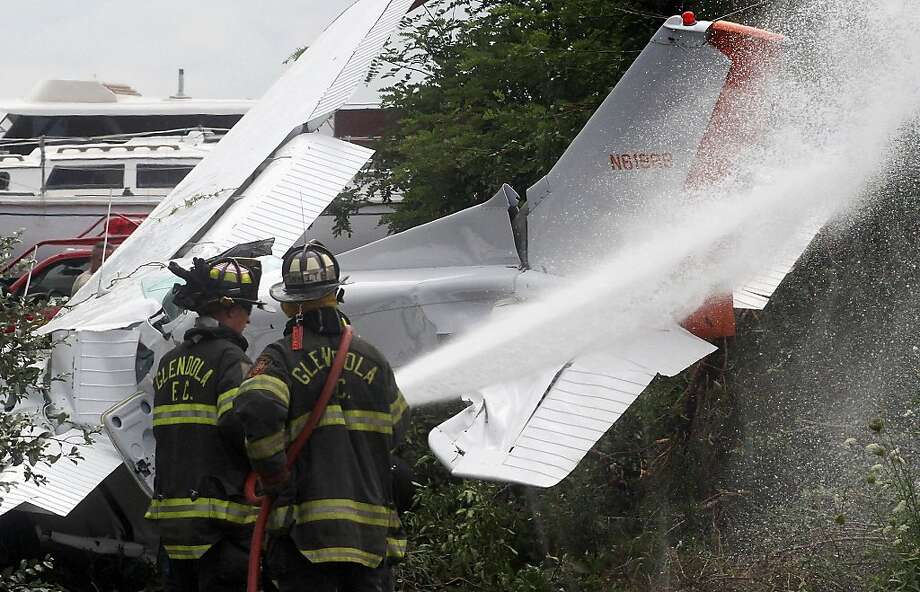 Glendola firefighters hose down a single engine advertising banner plane after it crashed at the north end of Monmouth Executive Airport in Wall, N.J. The pilot was the only person on board. Authorities say he sustained minor injuries. (AP Photo/The Asbury Park Press, Tom Spader)  NO SALES Photo: Tom Spader, Associated Press