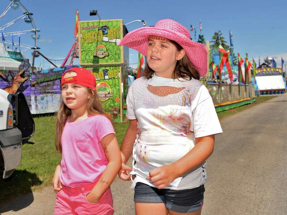 Sisters, Ava, 7, left, and Vanessa Webber of Cobleskill plan which rides they'll go on at the Schoharie County Sunshine Fair Friday afternoon, July 26, 2013, in Cobleskill, N.Y. The fair opens Saturday. (John Carl D'Annibale / Times Union) Photo: John Carl D'Annibale / 00023173A