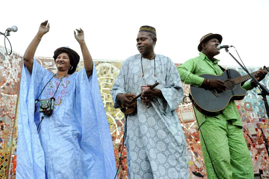 Fadimata Walet Oumar of the band Tartit, left, dances on stage with members of Mamadou Kelly during the Caravan for Peace concert on Friday, July 26, 2013, at Freedom Square in Troy, N.Y. Joining her are Youro Cisse, center, and band leader Mamadou Kelly. The tour of Malian musicians compliments the world renowned Festival au Desert held in northern Mali and hopes to raise awareness of the conflict in that country. The festival was forced into exile last year after Islamist extremists took over the region and Western music was banned. (Cindy Schultz / Times Union) Photo: Cindy Schultz / 00023278B