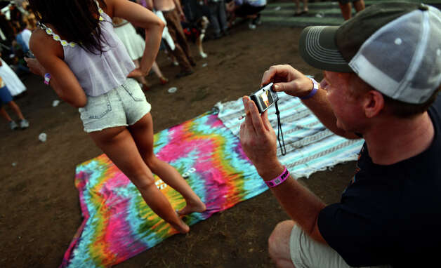 Ben Dranken, of Tuscaloosca, AL, snaps a picture of Bronte Uccellini's backside as they enjoy the 18th Annual Gathering of the Vibes music festival at Seaside Park in Bridgeport, Conn. on Friday July 27, 2013. Photo: Christian Abraham / Connecticut Post freelance