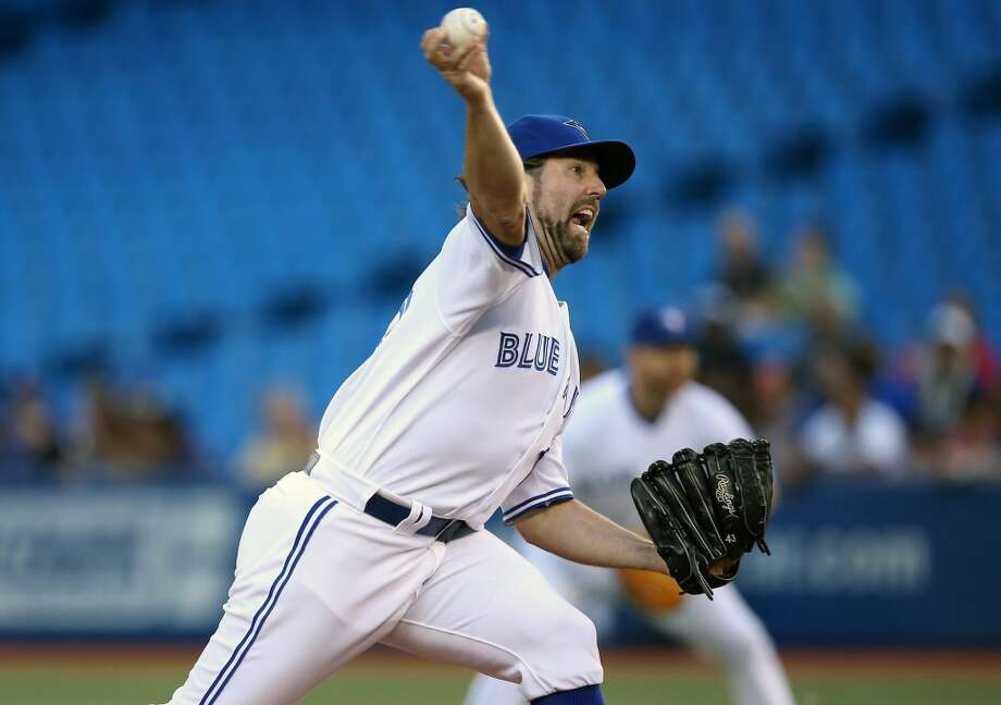 Blue Jays pitcher R.A. Dickey makes a throw to the Astros. Photo: Tom Szczerbowski, Getty Images