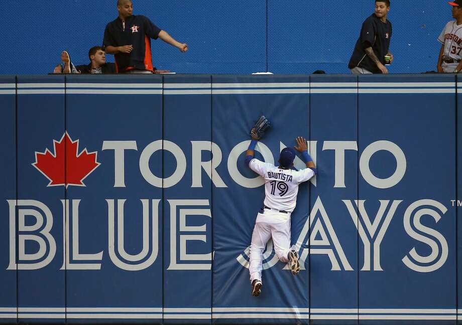 Jose Bautista of the Blue Jays is unable to get to a home run hit by Marc Krauss of the Astros. Photo: Tom Szczerbowski, Getty Images