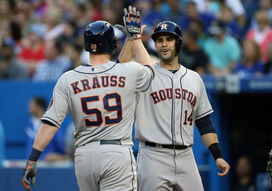 J.D. Martinez of the Astros congratulates Marc Krauss on his two-run home run during the second inning. Photo: Tom Szczerbowski, Getty Images