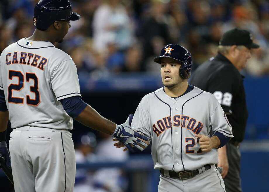Chris Carter of the Astros congratulates teammate Jose Altuve after scoring a run. Photo: Tom Szczerbowski, Getty Images