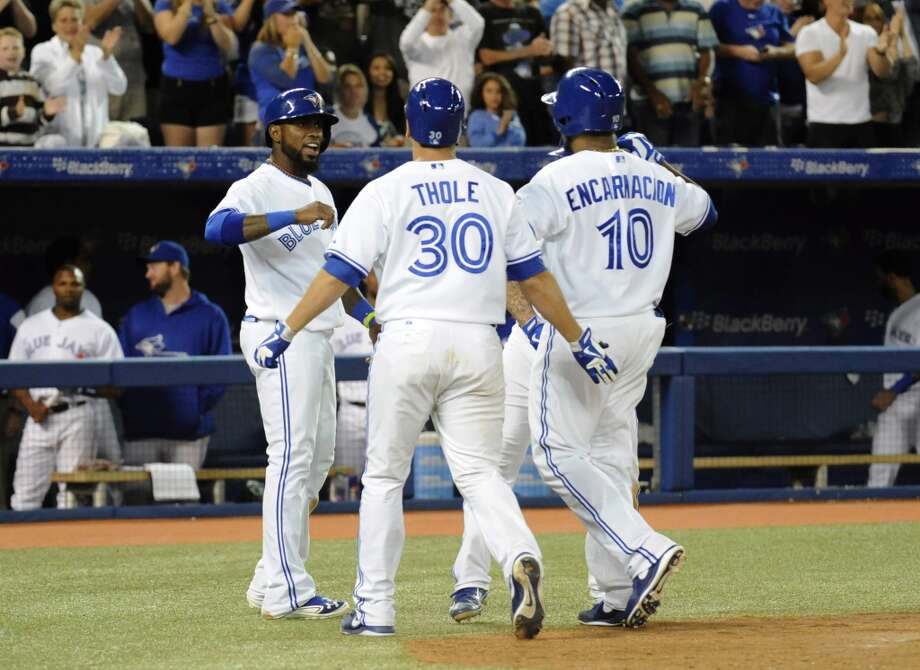 Blue Jays players celebrate Edwin Encarnacion's grand slam in the seventh inning. Photo: Jon Blacker, Associated Press/Canadian Press