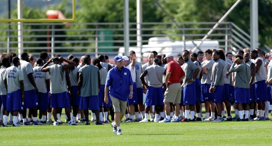New York Giants head coach Tom Coughlin, center, walks away as the team huddles after stretching during NFL football training camp in East Rutherford, N.J., Friday, July 26, 2013. (AP Photo/Julio Cortez) ORG XMIT: NJJC103 Photo: Julio Cortez / AP