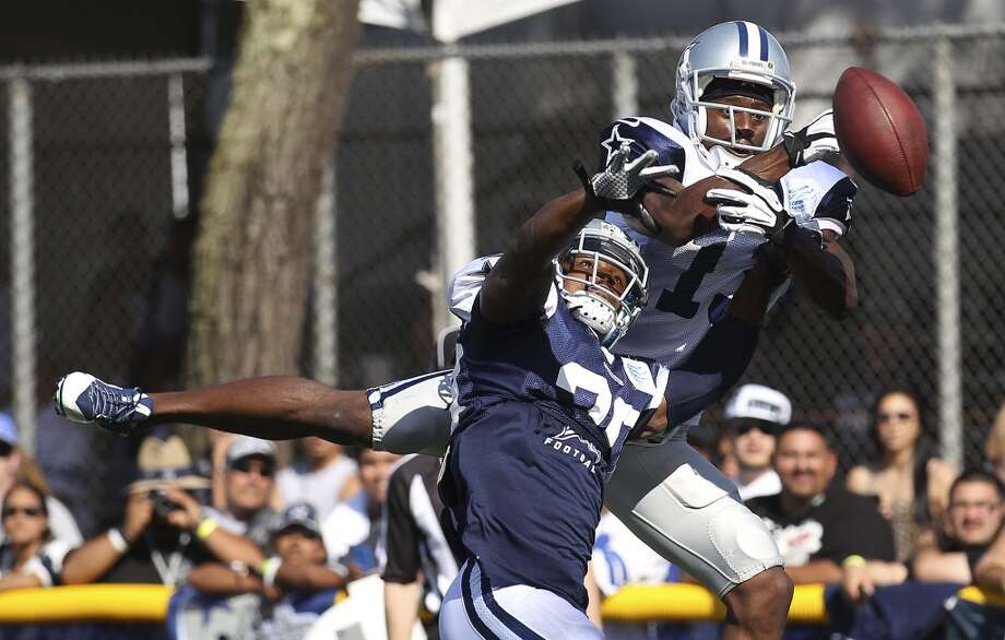 Cornerback B.W. Webb (20) breaks up a pass intended for receiver Anthony Armstrong (13) during the afternoon session of the 2013 Dallas Cowboys training camp on Friday, July 26, 2013 in Oxnard. (Kin Man Hui/San Antonio Express-News) Photo: Kin Man Hui, San Antonio Express-News