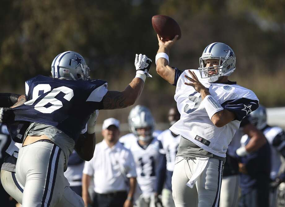 Quarterback Tony Romo (09) launches a pass over defensive tackle Nick Hayden (96) during the afternoon session of the 2013 Dallas Cowboys training camp on Friday, July 26, 2013 in Oxnard. (Kin Man Hui/San Antonio Express-News) Photo: Kin Man Hui, San Antonio Express-News