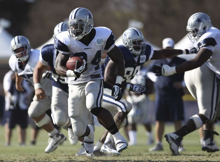 Running back Phillip Tanner (34) carries the ball during the afternoon session of the 2013 Dallas Cowboys training camp on Friday, July 26, 2013 in Oxnard. (Kin Man Hui/San Antonio Express-News) Photo: Kin Man Hui, San Antonio Express-News