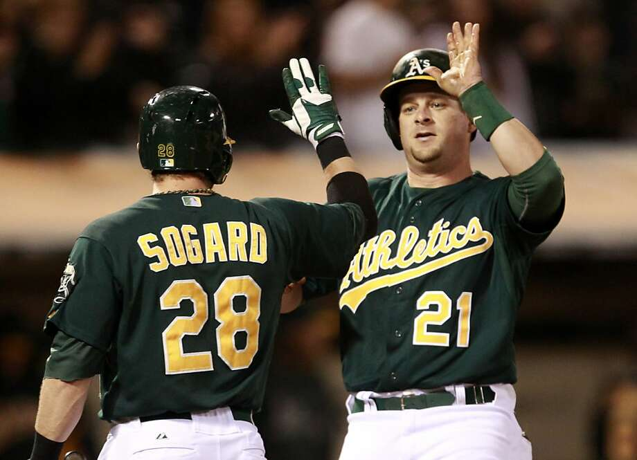 Eric Sogard congratulates Stephen Vogt on his two-run homer. Photo: Beck Diefenbach, Associated Press