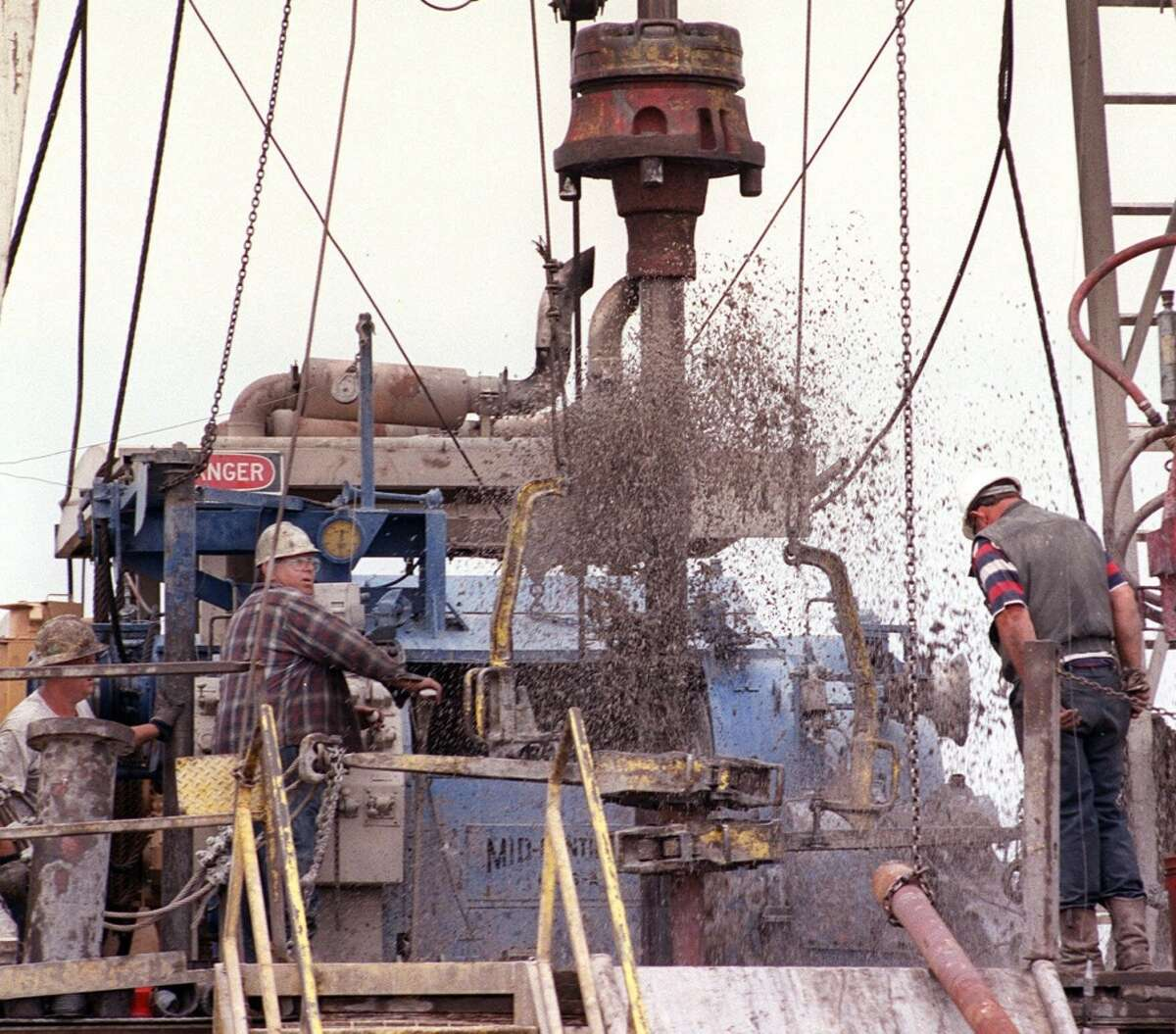 Drilling mud flies as drillers pull drilling pipe from a Mitchell Energy and Development Corp. well in Wise County, Texas on May 16, 2000.