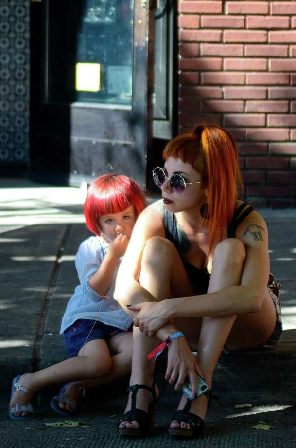 Jenni Ravetz and her daughter, Babette, take a break in the shade during the 2013 Capitol Hill Block Party Friday, July 26, 2013, in Seattle. Photo: SY BEAN, SEATTLEPI.COM / SEATTLEPI.COM