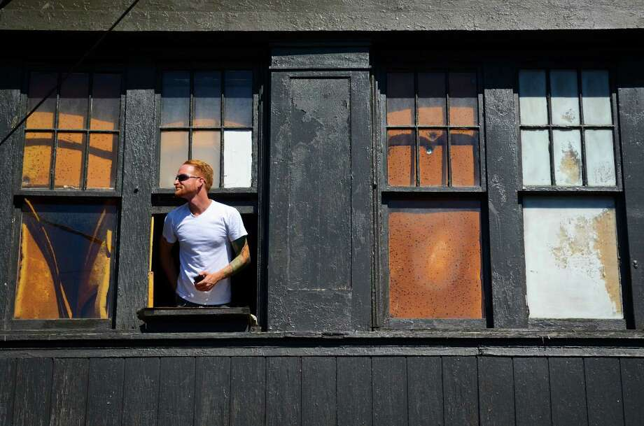 A man looks over the Vera Project stage out of an apartment window at the 2013 Capitol Hill Block Party Friday, July 26, 2013, in Seattle. Photo: SY BEAN, SEATTLEPI.COM / SEATTLEPI.COM