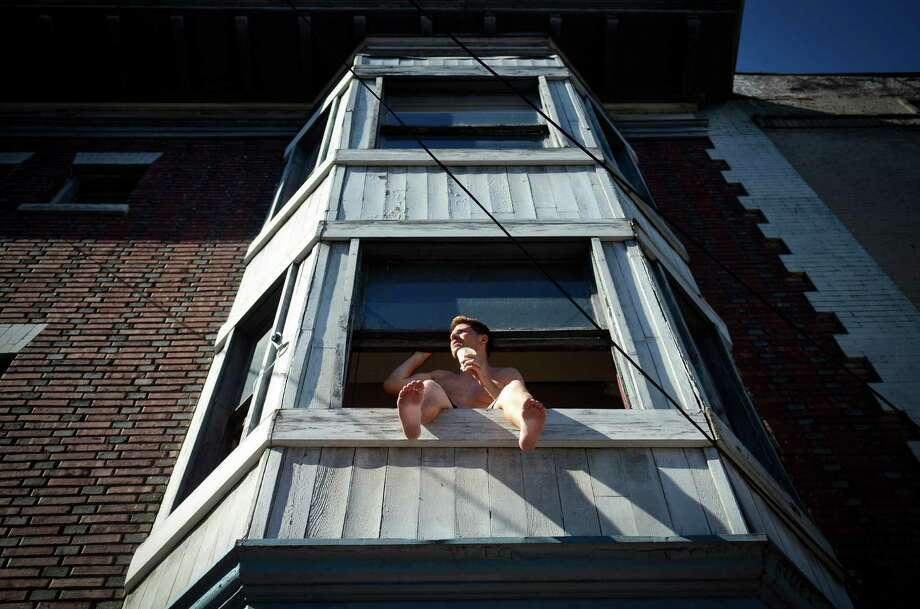 A man watches the main stage from an apartment window during the 2013 Capitol Hill Block Party Friday, July 26, 2013, in Seattle. Photo: SY BEAN, SEATTLEPI.COM / SEATTLEPI.COM