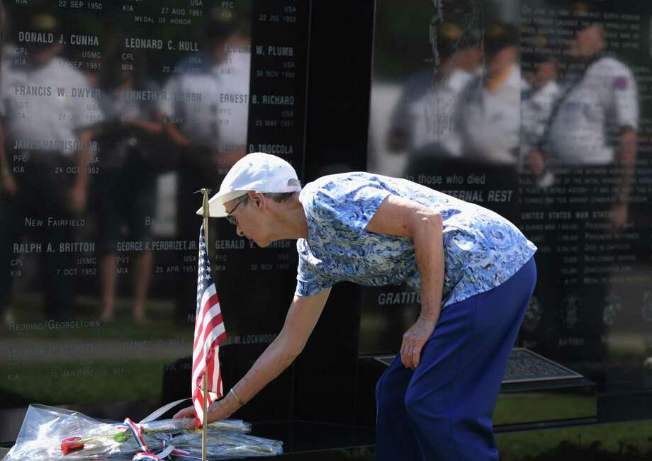 Rose Bennett, of Danbury, places flowers for fallen soldier James Harrison, Jr. during the Korean War Memorial Ceremony at Rogers Park in Danbury, Conn. on Saturday, July 27, 2013.  The ceremony celebrated the 60th anniversary of the armistace, thanking those who fought and remembering those who died during the Korean War. Photo: Tyler Sizemore / The News-Times