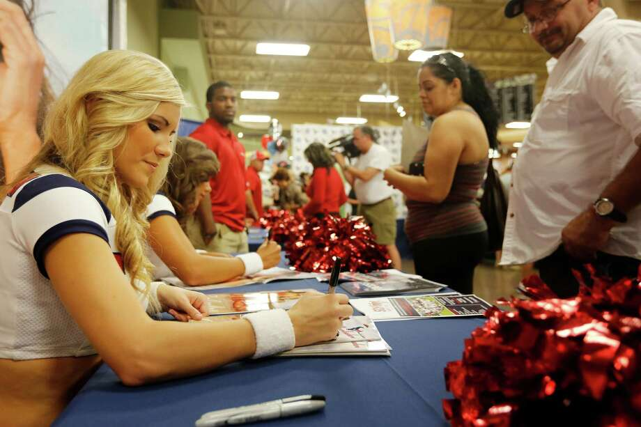 Texans cheerleader Kayla, signs a calendar for a fan, during an event unveiling the 2013-2014 Houston Texans cheerleader swimsuit calendar, Saturday, July 27, 2013 at the Kroger grocery store in the Heights neighborhood of Houston, Texas.  Photo: © TODD SPOTH, 2013 / © TODD SPOTH, 2013