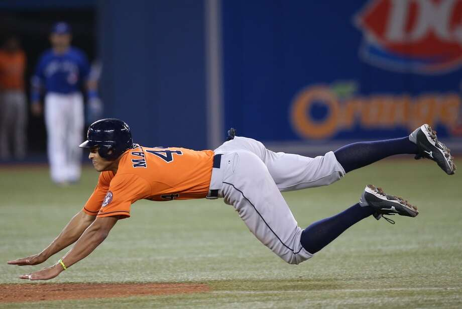 Astros outfielder Justin Maxwell steals a base against the Blue Jays. Photo: Tom Szczerbowski, Getty Images