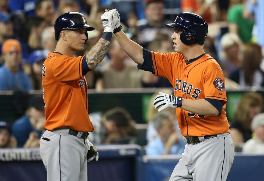 Astros third baseman Matt Dominguez is congratulated  by teammate Brandon Barnes after hitting a home run. Photo: Tom Szczerbowski, Getty Images