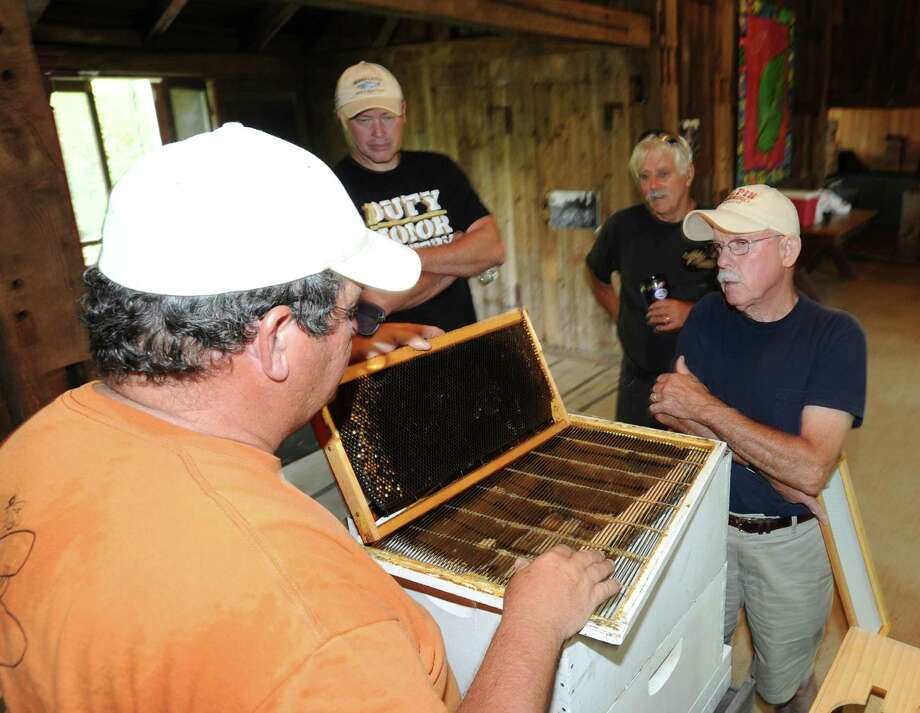 At left, Jeff Brown of Greenwich, a master beekeeper, discusses the average six-week life span of the honey bee with Greenwich resident, John Halpin, right, during a honey bee educational program hosted by the Backyard Beekeepers Association at Audubon Greenwich, Saturday, July 27, 2013. Photo: Bob Luckey / Greenwich Time