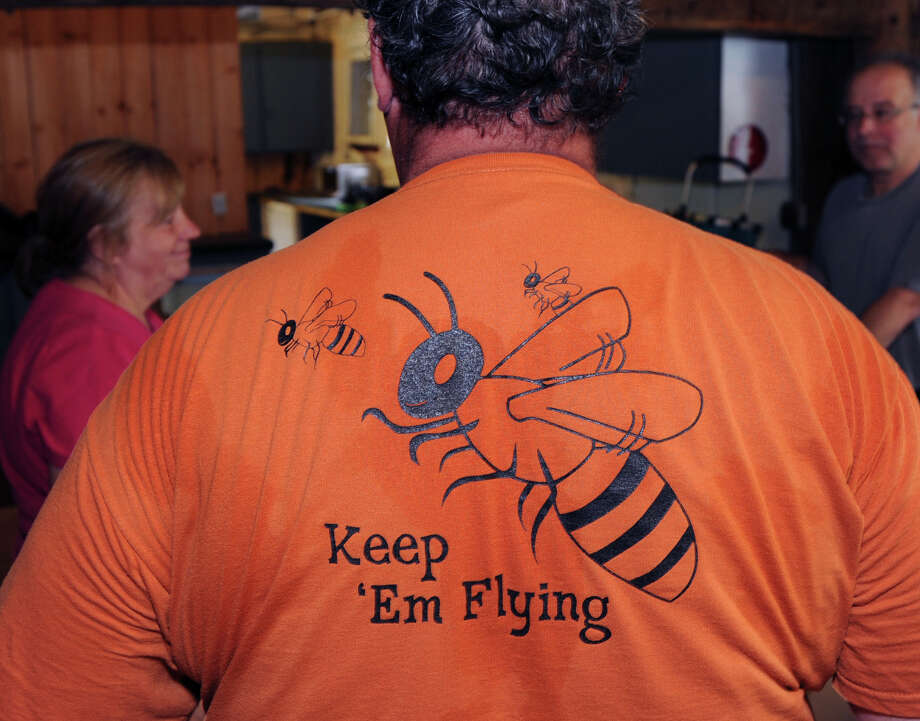 """Keep 'Em Flying,"" reads the shirt of Jeff Brown, a master beekeeper of Greenwich, during a honey bee educational program hosted by the Backyard Beekeepers Association at Audubon Greenwich, Saturday, July 27, 2013. Photo: Bob Luckey / Greenwich Time"