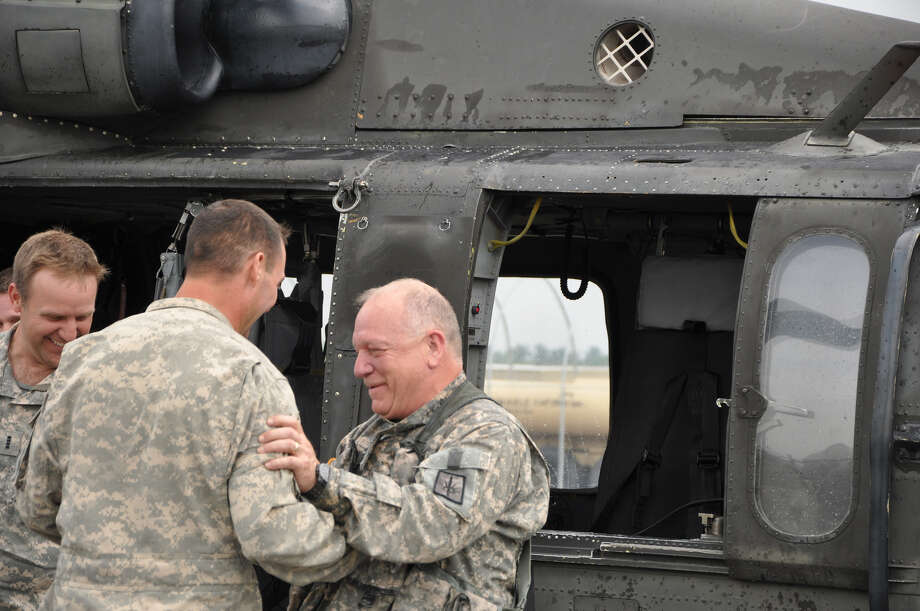 Division of Military and Naval Affairs Soldiers greet Army National Guard Chief Warrant Officer 5 Brian Smith, right, a helicopter pilot, upon completion of his final flight at the Albany International Airport after 40 years of duty before retirement.