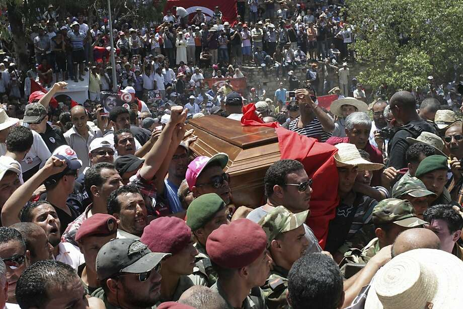 Tunisians carry the coffin of opposition politician Mohammed Brahmi during his funeral at Jellaz Cemetery in Tunis. He was shot 14 times in front of his home within sight of his family. Photo: Amine Landoulsi, Associated Press