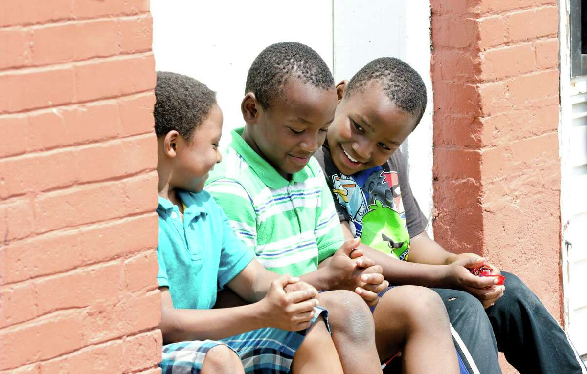 Stamford youths Jordan Lance Perry, 9; Samuel Fefe, 9, and his twin brother, Daniel Fefe, 9, sit in a doorway enjoying a bag of Skittles as the Stamford and Norwalk NAACP Branches Unite for âÄúStop the Violence / We are TrayvonâÄù Rally at the corner of Richmond Hill Avenue and Rose Park Avenue in Stamford on Saturday, July 27, 2013.