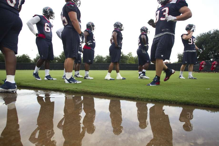 Texans defensive linemen are reflected in a puddle of water next to the practice field during the second day of training camp. Photo: Brett Coomer, Houston Chronicle